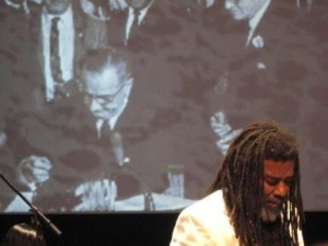 Wadada_Leo_Smith_in_front_of_projection_of_LBJ_signing_Voting_Rights_Act__1964_Ten_Freedom_Summers__October__2011_copyright_2011_Lyn_Horton_depth1